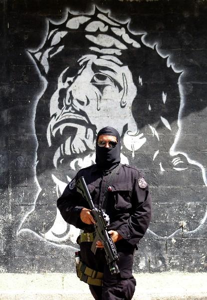 Un policía posa frente a uno de los graffitis pintados por pandilleros en la capital salvadoreña. (Foto Prensa Libre: Hemeroteca PL)