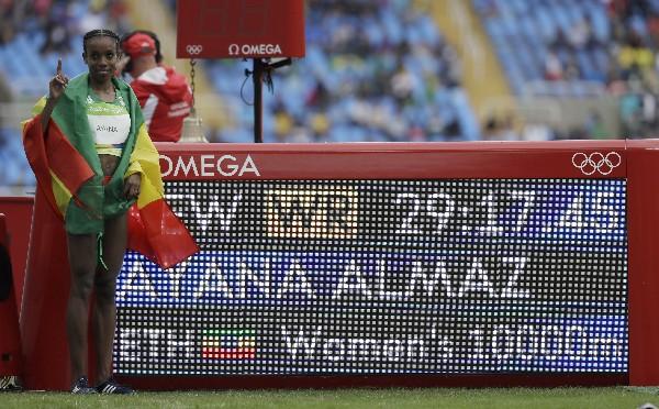 Almaz Ayana posa junto a la pantalla donde se muestra su récord logrado en los 10,000 metros planos. (Foto Prensa Libre: AP)