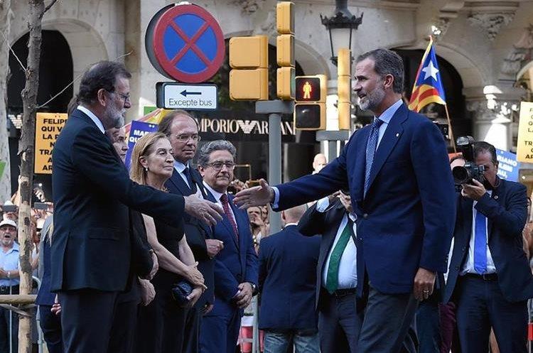 El Rey Felipe VI (d) de España saluda a Mariano Rajoy (i) durante una marcha contra el terrorismo. (AFP).