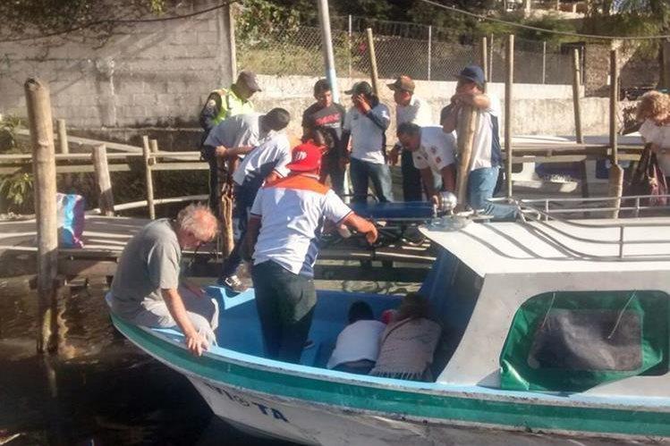 Socorristas voluntarios atienden a turista en muelle de Panajachel, Sololá. (Foto Prensa Libre: Ángel Julajuj)