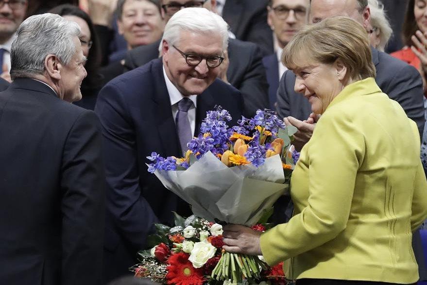 El nuevo presidente de Alemania, Frank-Walter Steinmeier, centro, es felicitado por por el presidente saliente, Joachim Gauck, izquierda, y la canciller alemana Ángela Merkel, derecha. (Foto Prensa Libre: AP)