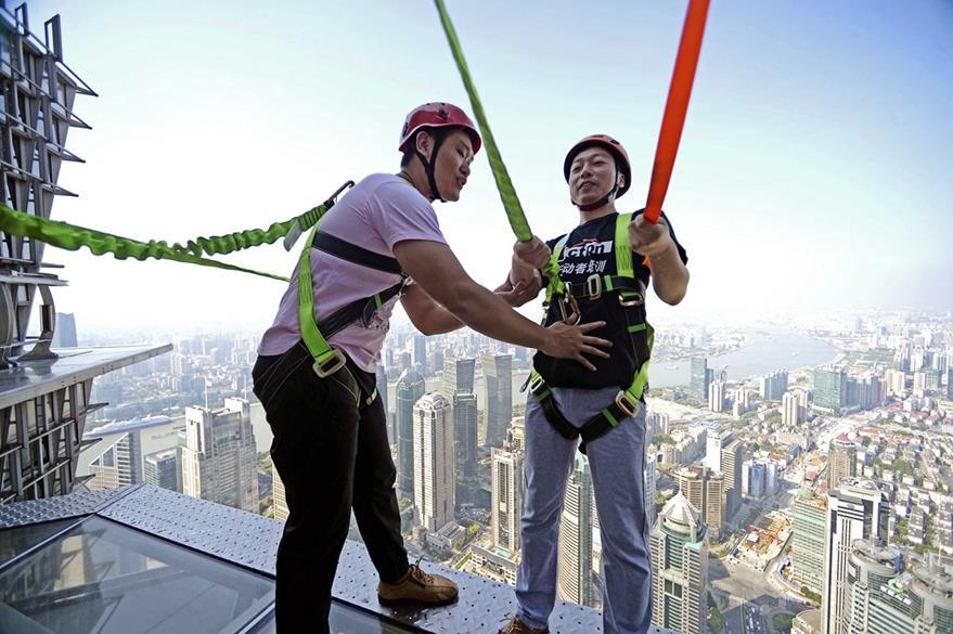 Dos personas caminan sobre la pasarela acristalada en el piso 88 de la Torre Jinmao en Shanghái, China. (Foto Prensa Libre: EFE).