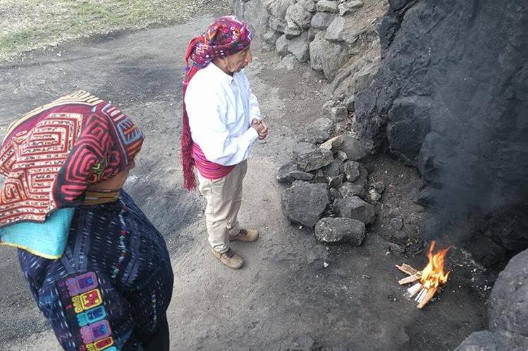Los guías espirituales Carlos Escalante y José García encienden un fuego sagrado en el altar Kaq K'axol, en Llanos del Pinal, Quetzaltenango. (Foto Prensa Libre: Fred Rivera)