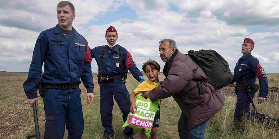 Osama Abdul Mohsen, el inmigrante sirio cuando cruzaba la frontera húngara con su hijo. (Foto: Hemeroteca PL).
