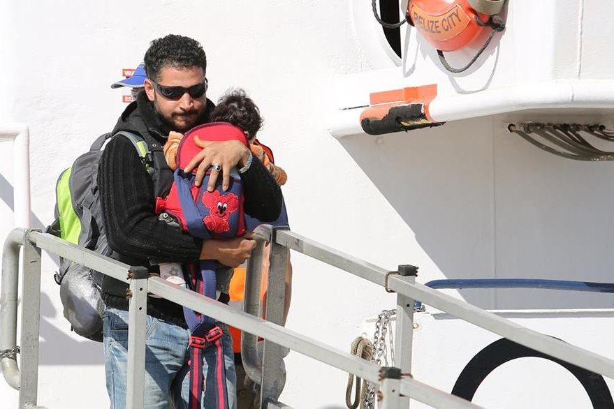 Un hombre desciende de la embarcación que lo trasladó con su bebé en brazos. Miles de niños son arriesgados a diario en el Mediterráneo. (Foto Prensa Libre: AP).