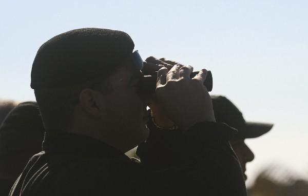 Un oficial mira a través de sus binoculares el avión Afriqiyah Airways. (EFE).