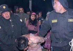 Agentes policiales  llevan a hombre vapuleado por pobladores de Totonicapán. (Foto Prensa Libre: Édgar Domínguez)