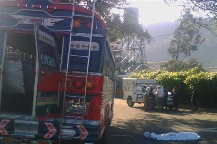 Autobús que fue tomado por asalto en Palín; a un costado el cadáver del pasajero que murió baleado. (Foto Prensa Libre: Enrique Paredes).