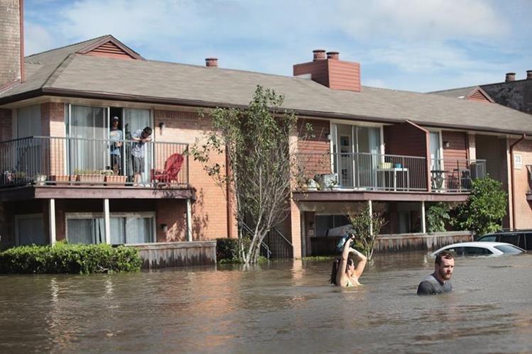 Residentes de Houston, Texas, esperan ser rescatados tras el paso de la tormenta Harvey. (Foto Prensa Libre: AFP)