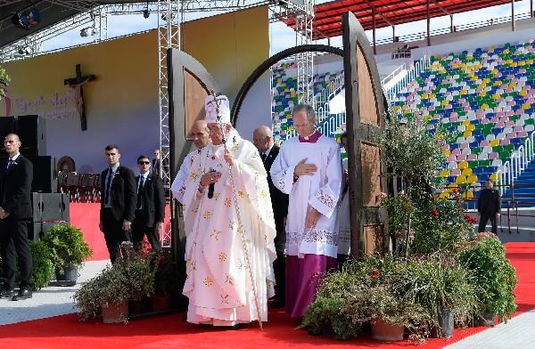 El Papa (c) cruza la puerta santa a su llegada para celebrar la misa en Tbilisi, Georgia. (EFE).