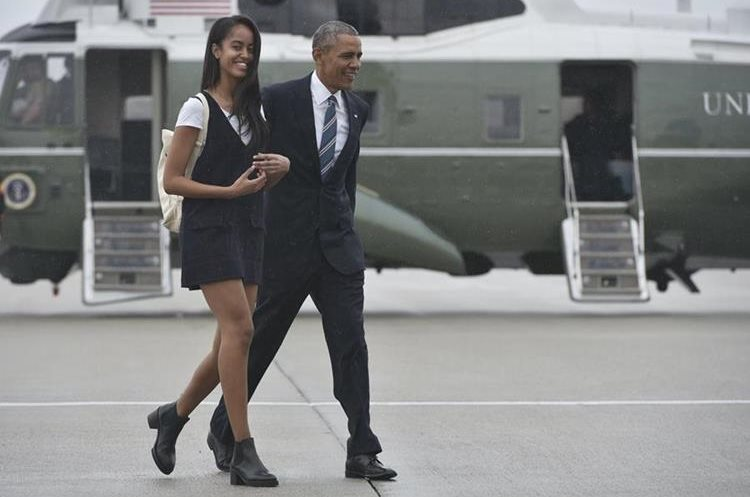 US President Barack Obama and daughter Malia make their way to board Air Force One before departing from Los Angeles International Airport in Los Angeles on April 8, 2016.  Obama is heading to San Francisco to take part in a Democratic National Committee roundtable discussion and to attend a Democratic Congressional Campaign Committee fundraiser. / AFP PHOTO / MANDEL NGAN