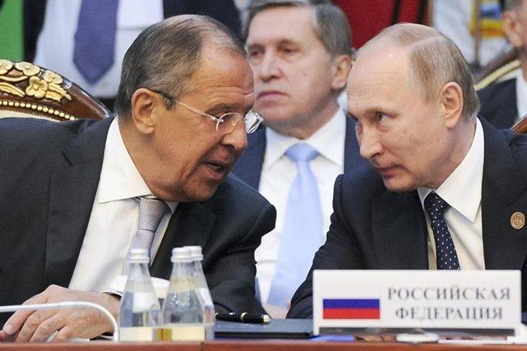 El canciller ruso Sergey Lavrov (i) conversa con el presidente Vladimir Putin (d). Foto Prensa Libre: AP