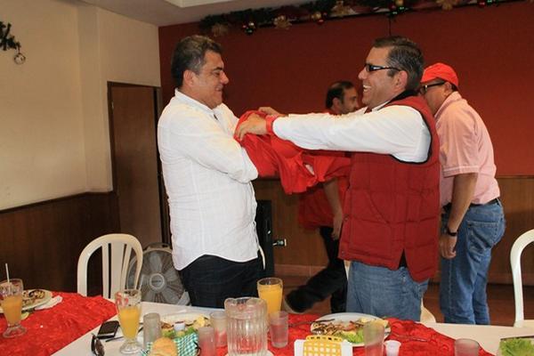 <p>Hernán Morán, diputado por Escuintla, se coloca la camisa roja con la ayuda de Manuel Baldizón de Líder. (Foto Prensa Libre: Enrique Paredes)<br></p>