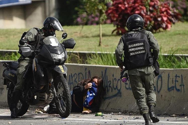 Efectivos arrestan a una manifestante en Caracas, Venezuela. (Foto Prensa Libre: AFP)