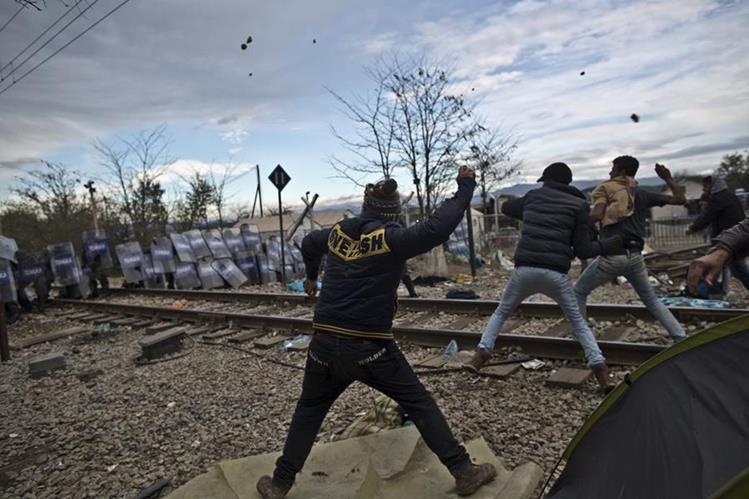 Migrantes atacan a pedradas a la policía macedonia. (Foto Prensa Libre: AP)