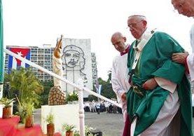 """El papa Francisco sube al altar donde ofició la misa en la Plaza de la Revolución; al fondo, la bandera cubana y la imagen del """"Che"""" Guevara. (Foto Prensa Libre: AP)."""