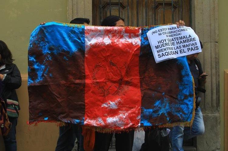 Una bandera de Guatemala manchada de rojo fue utilizado durante la protesta.