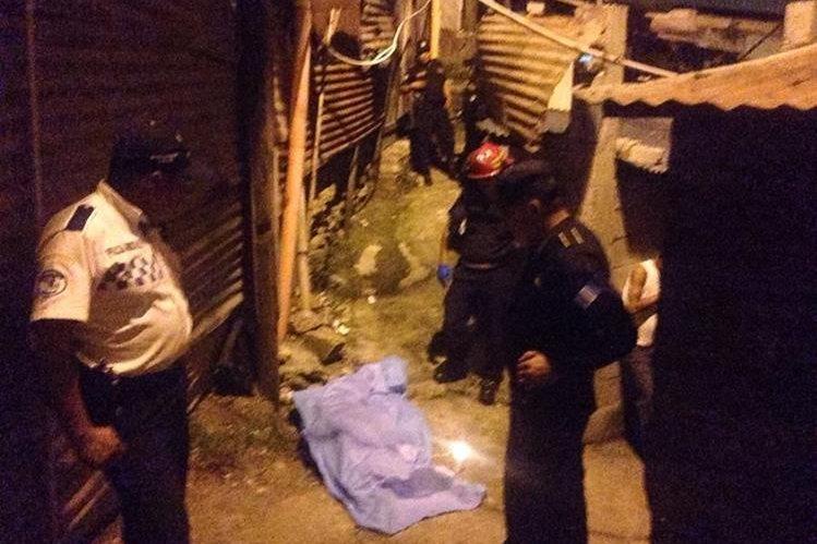 Bomberos y policías alrededor del cadáver de un hombre, muerto a balazos en Villalobos, zona 12 de Villa Nueva. (Foto Prensa Libre: CBM)