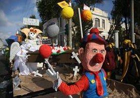Muñecos vestidos de payaso que simulan al presidente Morales, pancartas del muro que prevé construir Estados Unidos fue parte de la mofa. (Foto Prensa Libre: EFE)