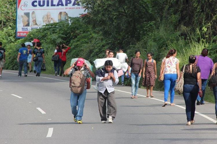Con sus productos en la espalda, las personas intentan llegar a sus destinos.