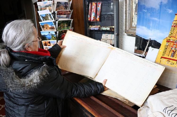 María Eugenia Miralbés, propietaria del Hotel Modelo, muestra el libro en el que se registró el poeta chileno Pablo Neruda, en 1950. (Foto Prensa Libre: María José Longo)