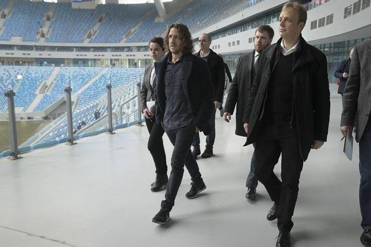 El exjugador español Carles Puyol acompaña a delegados de la Fifa a una inspección al estadio de San Petesburgo. (Foto Prensa Libre: AP)