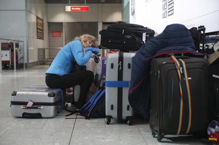 Algunos pasajeros, en su desesperación, durmieron sobre sus maletas. (Foto Prensa Libre: AFP)