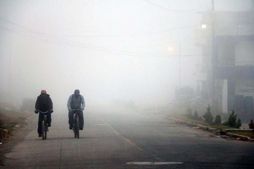 Vecinos de Xela se dirigen a sus lugares de trabajo entre la niebla. (Foto Prensa Libre: Carlos Ventura)