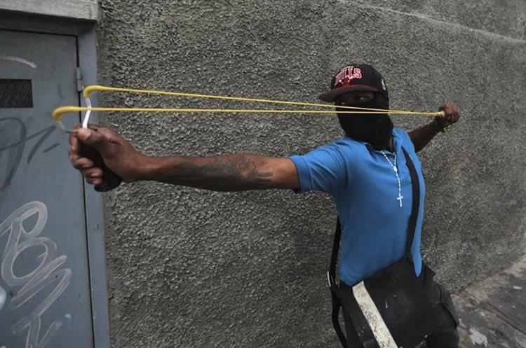 Un joven venezolano usa una honda como su única arma para defenderse de los ataques de la Policía en Caracas.