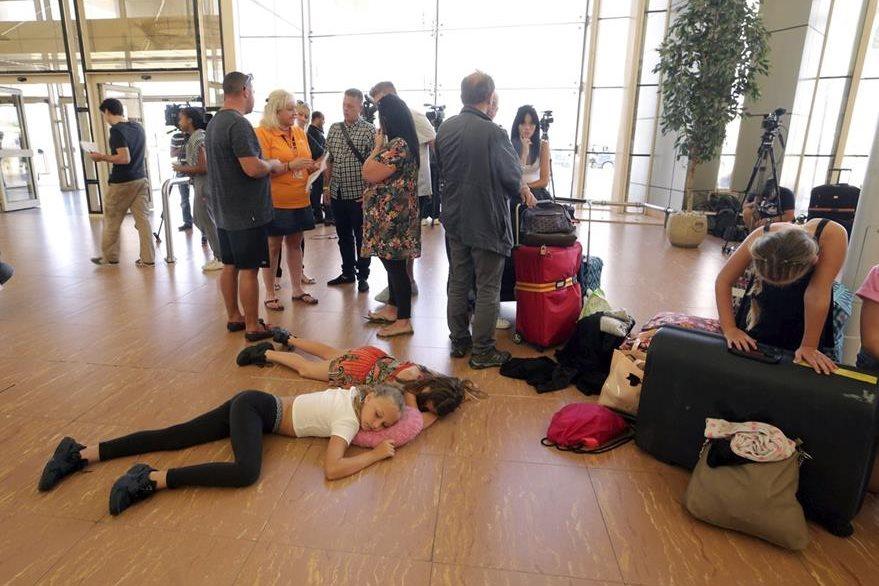 Desesperados, muchos turistas decidieron tomar una siesta en el suelo. (Foto Prensa Libre: EFE).