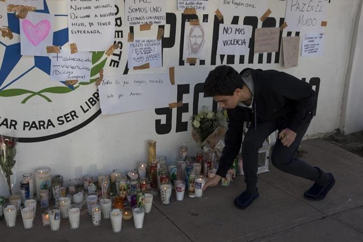 Un estudiante coloca una veladora en las instalaciones de la escuela donde ocurrió la balacera en Monterrey, México. (Foto Prensa Libre: EFE).