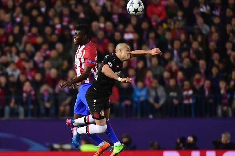 El delantero mexicano Javier Hernandez (d) disputa el esférico con Thomas Partey, del Atlético Madrid, en duelo disputado en el estadio Vicente Calderón (Foto Prensa Libre: AFP)