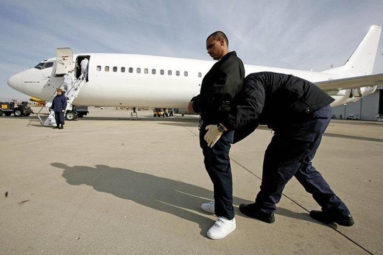 Un agente de inmigración acompaña a indocumentado antes de ser deportado en Chicago. (Foto Prensa Libre:AP).