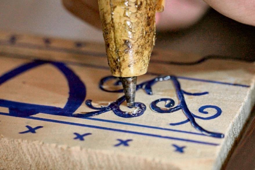 Para simular  decoraciones talladas en relieve en el anda, se hacen trazos que se contornean con silicón.