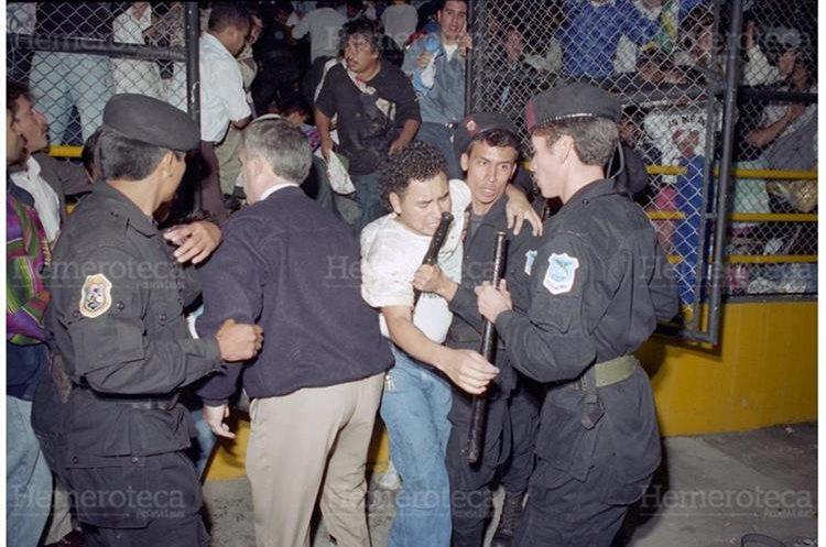 Bomberos ayudan a varios aficionados a salir luego de la avalancha que se produjo en los graderíos de la entrada sur donde fallecieron 83 aficionados. (Foto: Hemeroteca PL)