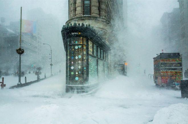 """""""El icónico edificio Flatiron de la ciudad de Nueva York emerge de la ventisca, como la proa de un buque gigante que se abre camino a través del viento y la nieve"""", describe lo que se ve en esta fotografía su autor, Michele Palazzo. Tomada durante la histórica tormenta costera Jonas, el 23 de enero de 2016, la fotografía se viralizó durante los días posteriores a la tormenta. MICHELE PALAZZO"""