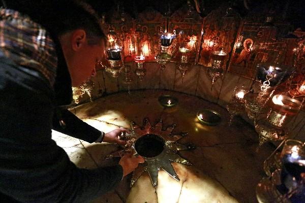 Un devoto reza delante de la venerada estrella de Belén. (EFE).