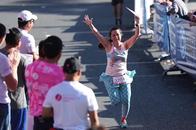 Una de las participantes levanta los brazos al final de la carrera.
