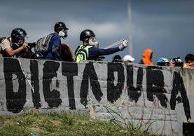 Opositores de enfrenta con la Policía antidisturbios en Caracas.(Foto Prensa Libre:AFP).