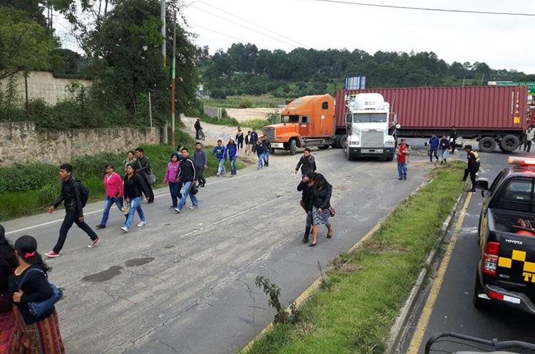 Pasajeros de autobuses optan por pasar el bloqueo caminando.