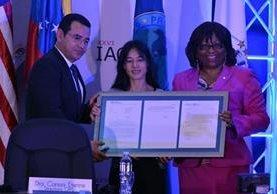 La directora de la OPS, Carissa Etienne, entrega la certificación de eliminación de oncocercosis a la ministra de Salud, Lucrecia Hernández y al presidente Jimmy Morales. (Foto Prensa Libre: Ministerio de Salud).