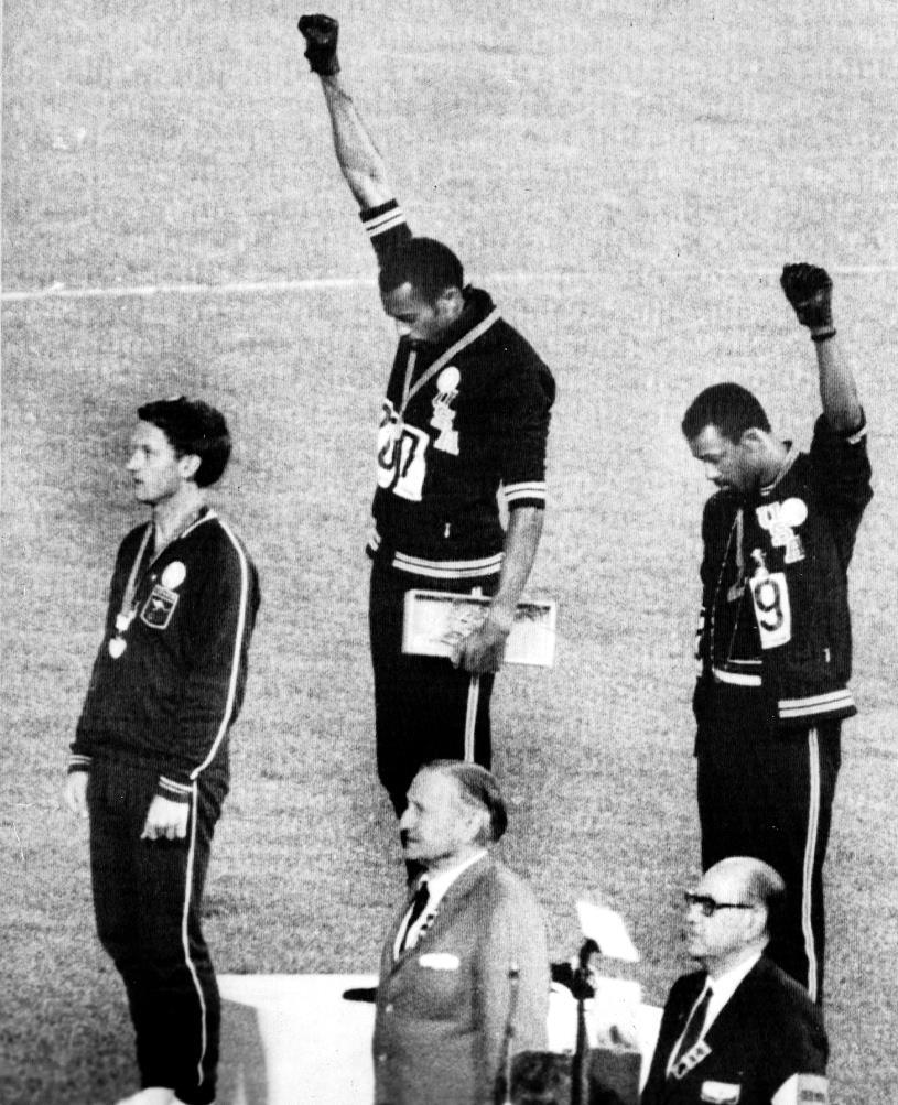 """Los atletas estadounidenses Tommie Smith y Joh Carlos quedaron en primer y segundo lugar en prueba de 200 metros lisos, levantan el brazo en alto, símbolo del """"Black Power"""" o """"Poder Negro"""" en los Juegos Olímpicos de México 1968. (Foto: EFE)"""