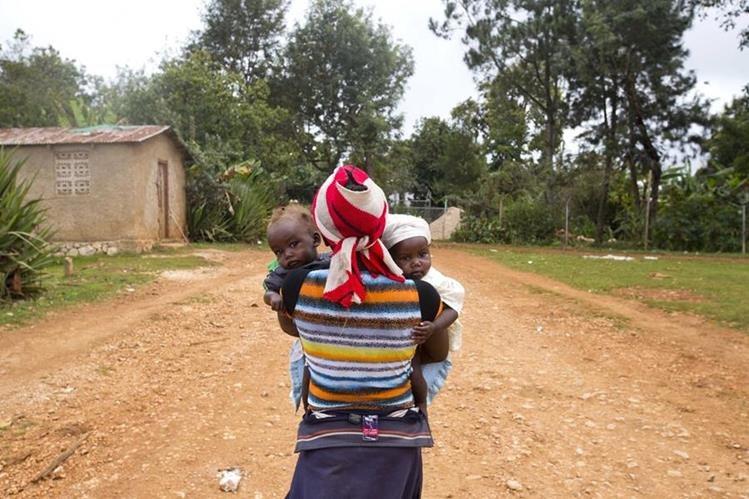 Una mujer sostiene en brazos a sus dos hijos a quienes ya no sabe con qué alimentar. (Foto Prensa Libre: AP).