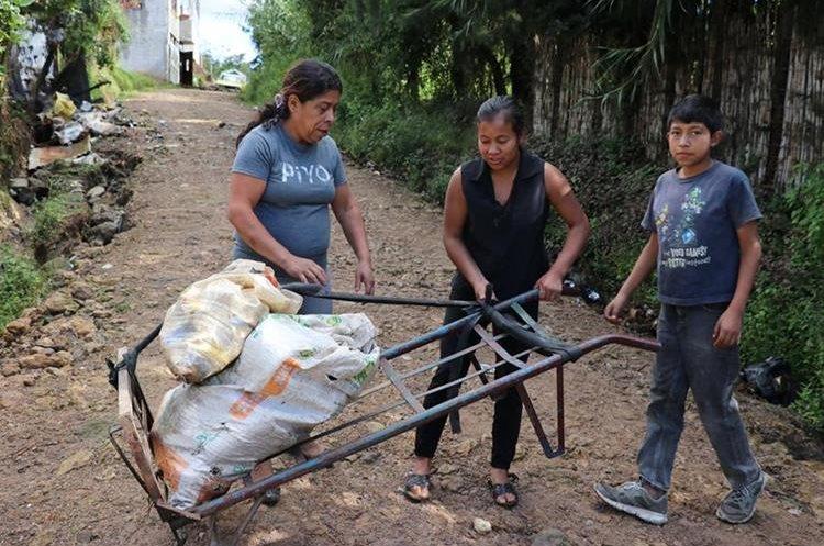 Ángela Vielman junto a su nuera y su nieto trabajan en la recolección de chatarra y latas. (Foto Prensa Libre: Héctor Cordero)