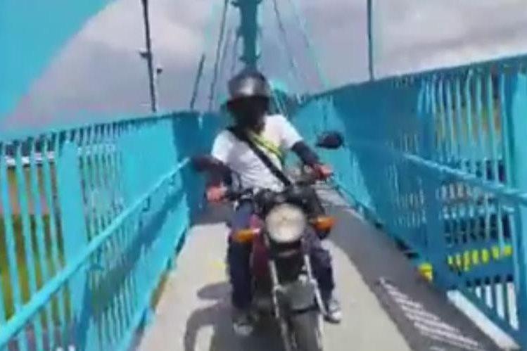 Un motorista es captado al momento de circular en una pasarela. (Foto Prensa Libre: Facebook)