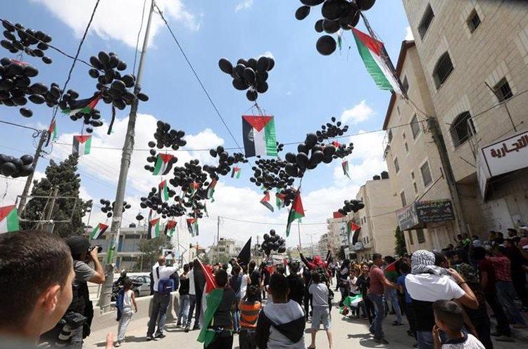 Palestinos lanzaron globos negros que llevaban banderas de Palestina, durante una protesta en Cisjordania. (Foto Prensa Libre: EFE)