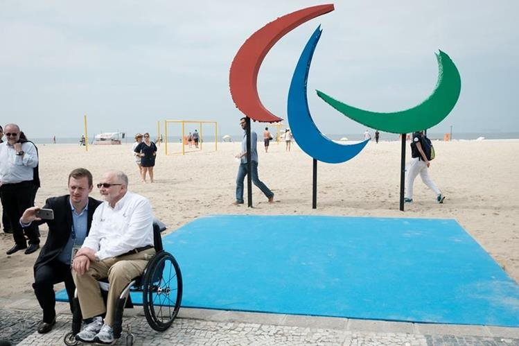 Philip Craven, Presidente del Comité Paralímpico Internacional posa junto a Andrew Parsons, Presidente del Comité Paralímpico de Brasil frente a una escultura. (Foto Prensa Libre: AFP)