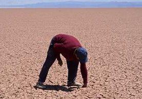 Un hombre inspecciona un sector del lago Poopó en Ouroro, convertido ahora en desierto. (Foto Prensa Libre: EFE).