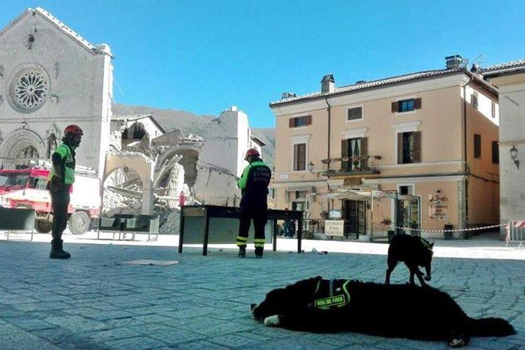 Socorristas observan los daños causados en la Iglesia de San Benito en Norcia, de la cual en pie quedó solo la fachada. (Foto Prensa Libre: EFE)