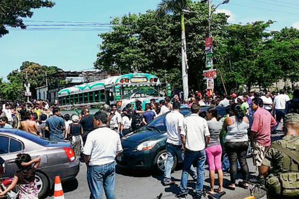 Vecinos de la zona 5 de la cabecera de Escuintla se acercan a la escena del crimen, donde un piloto de autobús murió baleado. (Foto Prensa Libre: Carlos Enrique Paredes)